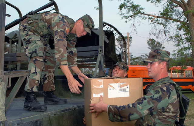 US Army (USA) Soldiers assigned to the 1345th Transportation Company, 90th Troop Command, Oklahoma Army National Guard (OKARNG), load supplies onto a transport truck at a staging area in New Orleans, Louisiana (LA), during Hurricane Katrina relief operations. Pictured left-to-right: Specialists (SPC) Tanner Dupree; Sergeant (SGT) Todd Garner, and SGT Jeremy Killman. (A3570)