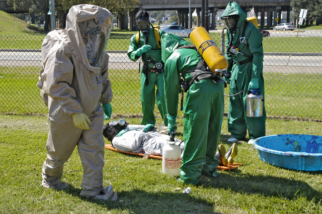 """[Hurricane Katrina/Hurricane Rita] Baton Rouge, La., October 9, 2005 - As one member of a HAZMAT rescue team approaches a disinfectant pool, other members of a decontamination team tend to a """"rescued"""" training victim.  These personnel from an area Emergency Madical Technician team are undergoing resonse and rescue training similar to that undergone by HAZMAT teams cleaning up chemical and other hazardous spills caused by Hurricanes Katrina and Rita.  Win Henderson / FEMA"""