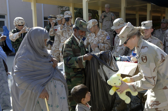 A U.S. Army Chaplain with the Combined Joint Task Force 76, Afghanistan, hands a Teddy Bear to a young Afghan boy while an Afghan civilian looks on during a visit to the Korean Army Hospital, Bagram Air Field, Afghanistan, Oct. 10, 2005. Members of the U.S Military are working to help the recovery of the people of Afghanistan. (U.S. Army photo by SPC. Christopher Admire) (Released)