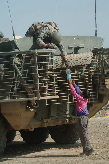 A US Army (USA) Soldier of the 172nd Stryker Brigade Combat Team, Fort Wainwright, Alaska (AK), onboard an M1126 Stryker Infantry Carrier Vehicle (ICV), hands an Iraqi boy a bottle of water in Mosul, Iraq, during Operation IRAQI FREEDOM. The Stryker is equipped with a Slat Armor cage