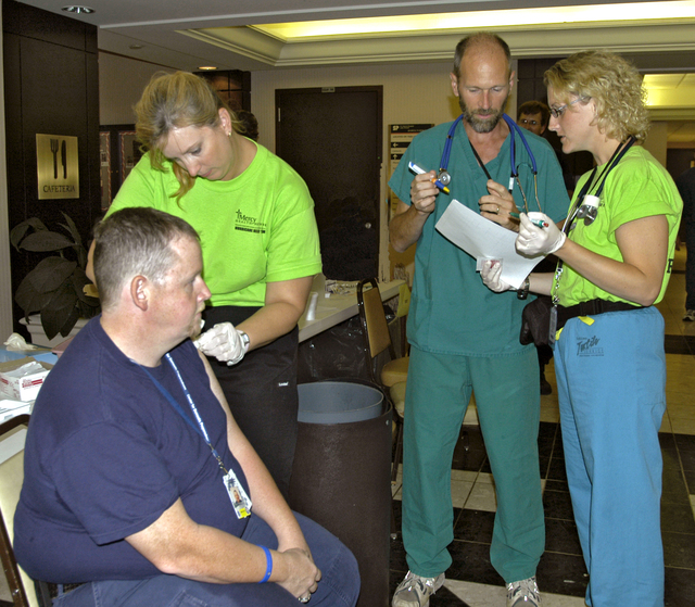 """[Hurricane Rita] Lake Charles, La., October 11, 2005 - As Walter Pendleton, a medic from Greenwich, Ct., gets ready to receive a Hepatitis """"A"""" innoculation from nurse Kecia Cowden of Des Moines, Ia., a Mercy Health Network nurse, another Mercy nurse, Gretchen Crooks (right) of Maso City, Ia. and Doctor Thoma Benzoni of Sioux City, Ia. review a patient's shot record.  These three Iowa medical personnel are in Louisiana as part of a Disaster Medical Assistance Team providing innoculations to disaster workers and people affected by Hurricanre Rita.  Win Henderson / FEMA"""