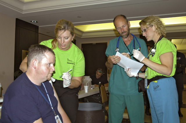 """[Hurricane Rita] Lake Charles, La., October 11, 2005 - While Mercy Health Network nurse Kecia Cowden of Des Moines, Ia., administers a Hepatitis """"A"""" innoculation to Walter Pendleton, a medic from Greenwich, Ct., another Mercy nurse, Gretchen Crooks (right) of Maso City, Ia. and Doctor Thoma Benzoni of Sioux City, Ia. review a patient's shot record.  These three Iowa medical personnel are in Louisiana as part of a Disaster Medical Assistance Team providing innoculations to disaster workers and people affected by Hurricanre Rita.  Win Henderson / FEMA"""