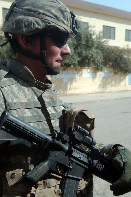 A soldier armed with a Squad Automatic Weapon (SAW), M249 Light Machine Gun, from A- Troop, 4-14 Cavalry, 172nd Stryker Brigade Combat Team (SBCT) patrols a dangerous neighborhood. The soldier keeps a sharp watch down a road the day before Iraqs elections. (U.S. Army photo by SPC. Jeffery Sandstrum) (Released)