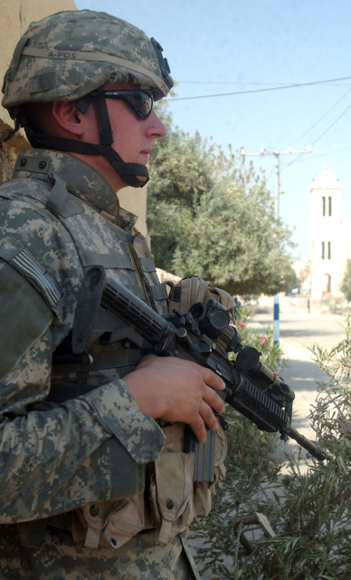 A soldier armed with an M4 carbine weapon, from A Troop, 4th Battalion, 14th Cavalry, 172nd Stryker Brigade Combat Team (SBCT), keeps a sharp watch down an empty road the day before Iraqi elections. (U.S. Army photo by SPC. Jeffery Sandstrum) (Released)