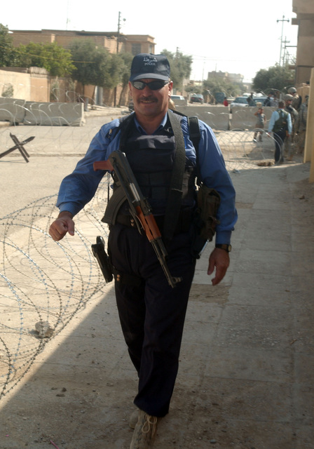 An armed, Iraqi policeman guards the entrance point to where the elections will be held.  In the background,  locals talk with soldiers patroling the area. (U.S. Army photo by SPC. Jeffery Sandstrum) (Released)