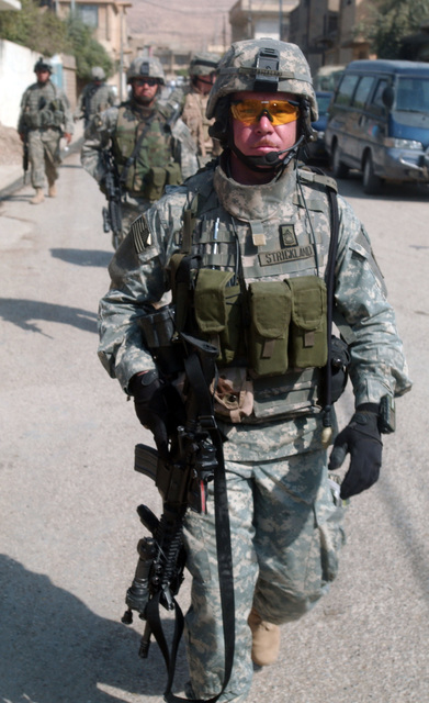 SGT. 1ST Class Strickland, the platoon leader, leads the way as his fellow comrades from A Troop, 4th Battalion, 14th Cavalry, 172nd Stryker Brigade Combat Team (SBCT) patrol a dangerous neighborhood during the Iraqi elections. The soldiers wearing full body gear are armed with M4 carbine weapons. (U.S. Army photo by SPC. Jeffery Sandstrum) (Released)