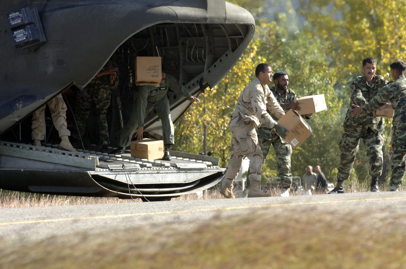 U.S. Army CPL. Amit Ranadey assists in unloading relief supplies from a U.S. Army CH-47 Chinook helicopter in the village of Rawala Kot, Pakistan, on Oct. 14, 2005.  The Department of Defense is participating in the multinational effort to provide humanitarian assistance and support to Pakistan and parts of India and Afghanistan following a devastating earthquake.  D(U.S. Army photo by SPC. Christopher Admire) (Released)