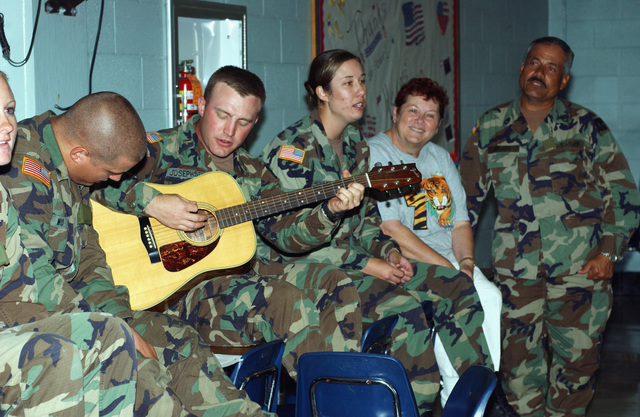 Wyoming Army National Guard (WYARNG) Second Lieutenant (2LT) Ben Josephson, 960th General Support Maintenance Company (GSMC), Torrington Wyoming (WY), sings and plays the guitar for employees of Harry S. Truman Middle School, as well as for Soldiers in Jefferson Parish, Louisiana (LA), during the Hurricane Katrina relief effort. (A3613)