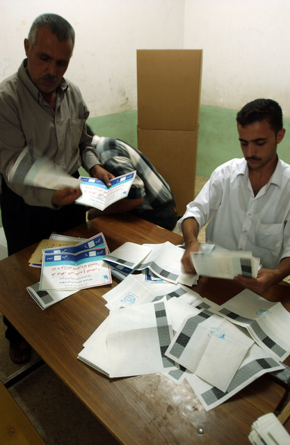 Iraqi election officals check and place the ballots into a ballot box after the elections on the constitutional referendum at a polling station. (U.S. Army photo by SPC. Jeffery Sandstrum) (Released)