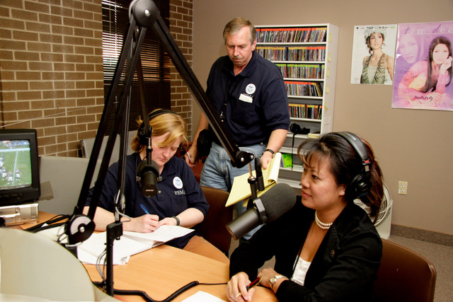 [Hurricane Rita] Houston, TX, October 16, 2005 -- Laurel Ryan, assistant Senior Federal Officer in Houston, confers with Charlie Hendereson, lead PIO, during an interview with Kathrine Bui on Little Saigon, a Houston radio station targeted at the local and evacuated Vietnamese population.  FEMA provides media services to special market media in several languages.  Photo by Ed Edahl/FEMA