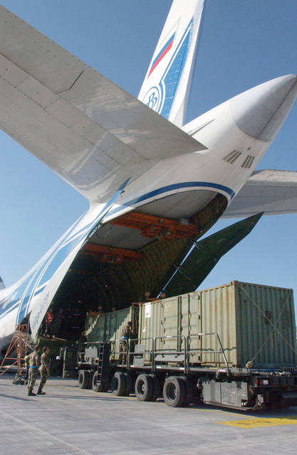 A Volga-Dnepr Airlines Antonov AN-124-100 Condor cargo aircraft sits parked at Ramstein Air Base (AB), Germany (DEU), as containers holding medical and personal gear for the US Army 212th Mobile Army Surgical Hospital (MASH) are offloaded from US Air Force (USAF) K-Loaders into the aircrafts open cargo area. The 212th MASH is the lead element of Task Force 212 (TF 212) and being airlifted into Pakistan (PAK) as part of a multinational humanitarian assistance effort in response to the 7.6 magnitude earthquake that hit Kashmir, Pakistan on October 8, 2005