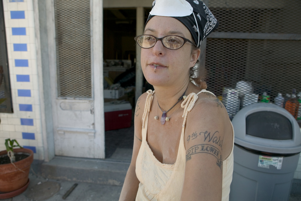 """[Hurricane Katrina] New Orleans, LA., 10/18/2005 -- Artist, Andrea Garland takes a break from  cleaning out her home and artist studio in Bywater following Hurricane Katrina. She reveals her new tatoo, """"9th Ward RIP"""", reflecting a central focus in the area, the question as to whether the 9th Ward will be rebuilt or not.  FEMA photo/Andrea Booher"""