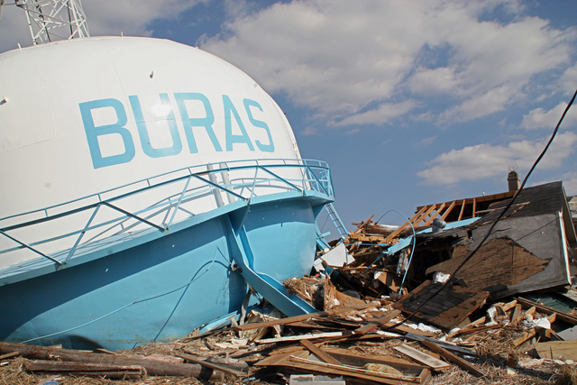 [Hurricane Katrina] Buras, LA, October 25, 2005 - The eye of Hurricane Katrina passed directly over this community. The water tower rests on top of a house in the ruins of Plaquemine Parish. Robert Kaufmann/FEMA