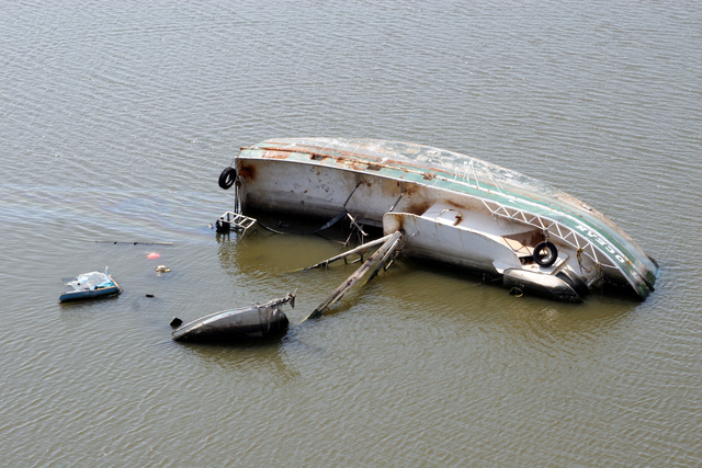 [Hurricane Katrina] Empire, LA, October 25, 2005 - This shrimp boat lies on its side in a few feet of water spilling its fuel into the waterway.  Almost 60 days after hurricane Katrina damage can be seen everywhere in Empire, LA.  Robert Kaufmann/FEMA