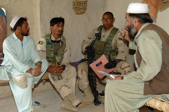 U.S. Army CAPT. Edward Hollis (right) 1ST BDE 504PIR Alpha Company Commander, and his interpreter (left), enquire information from local nationals about recent murder in Zanbar, Afghanistan on Aug. 27, 2005. The murder took place at the local mosque night prior to this meeting.(U.S Army photo by PFC. Michael Zuk) (Released)