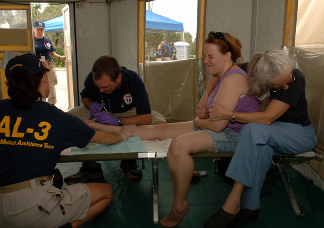 [Hurricane Wilma] Plantation, FL, October 28, 2005--Jesse Payne of Plantation, FL, second from right, is held by her mother, Barbara Payne, as FEMA Disaster Medical Assistance Team member, Dr. Tim Tonini, (OK-1), works on a toe injury with nurse Valerie Cottingham, (AL-3) . The DMAT is set up at Westside Regional Medical Center to help the flow of patients visiting the emergency room.  Jocelyn Augustino/FEMA