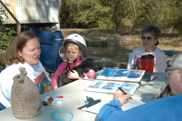 [Hurricane Katrina] Wiggins, Miss., October 29, 2005 -- Cheryl Rasbury (left) tells of the night her beachfront house was destroyed by Hurricane Katrina.  Her friend Gilda Tackett (right) and granddaughter Mariah (holding a puppy named FEMA) listen intently as FEMA worker Alan Jones takes notes.  George Armstrong/FEMA