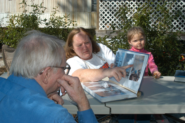 [Hurricane Katrina] Wiggins, Miss., October 29, 2005 -- In the yard of her mobile home Cheryl Rasbury shows photos of her destroyed beach home to FEMA employee Alan Jones, while her grand daughter Mariah looks on. FEMA grants enabled her to buy the home and replace the furniture lost in Hurricane Katrina.  George Armstrong/FEMA