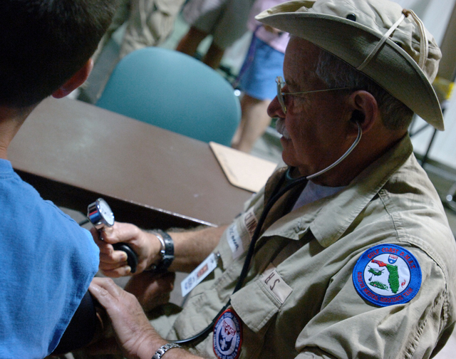 [Hurricane Wilma] Boynton Beach, FL, October 29, 2005 -- FEMA Disaster Medical Assistance Team parmedic Richard Clinchy, FL-1, checks the blood pressure of a patient outside of the JFK Medical Center.  The DMAT has set up a temporary emergency room at  the entry way of the hospital to assist in seeing the increase flow of patients due to Hurricane Wilma.  Jocelyn Augustino/FEMA