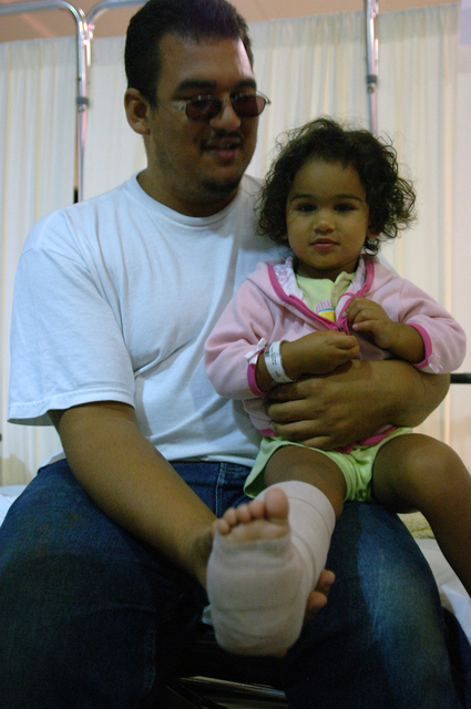 [Hurricane Wilma] Boynton Beach, FL, October 29, 2005 -- Genesis Nunez, sits in her father, Juan Nunez's lap after having her leg in a splint by a member of the FEMA Disaster Medical Assistance Team at the JFK Medical Center.  The DMAT is set up in the entry way of the hospital to assist in seeing the increase flow of patients due to Hurricane Wilma.  Jocelyn Augustino/FEMA