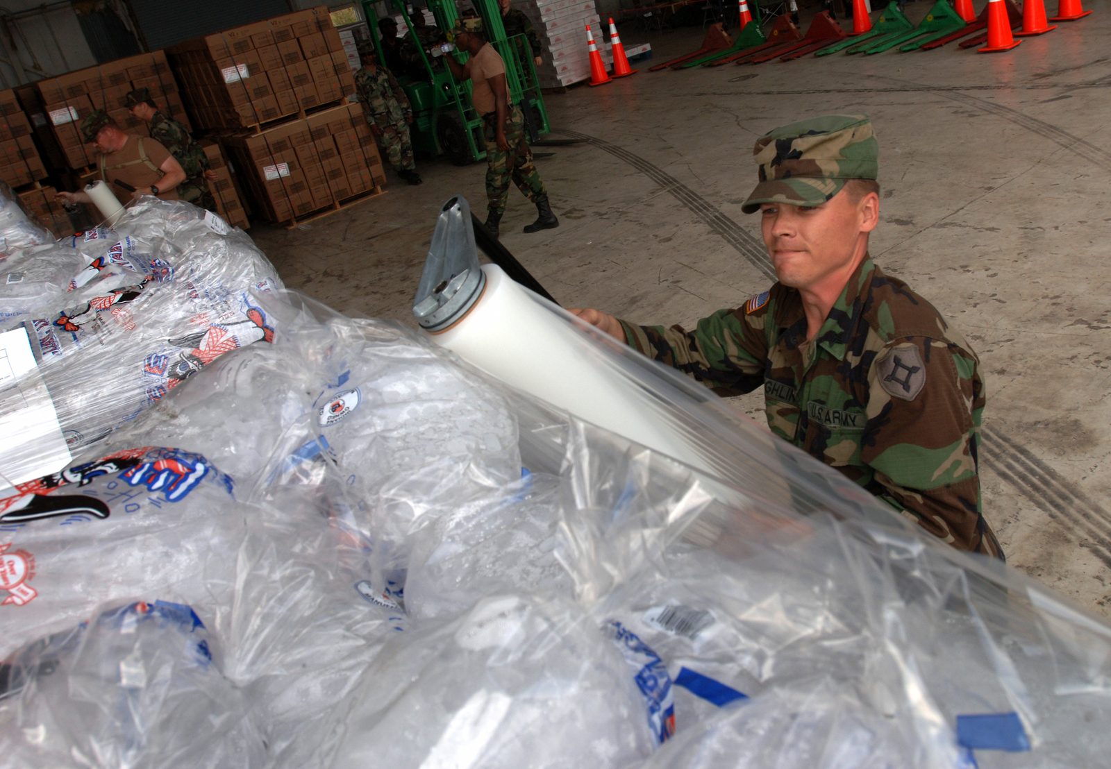 [Hurricane Wilma] Homestead, FL, October 30, 2005 -- National Guardsmen Steven Laughlin, of Ocala, wraps pallets of ice in a hanger at the Air Force Base which is being used as a staging area for both water and ice distribution for areas impacted by Hurricane Wilma.  Jocelyn Augusitno/FEMA
