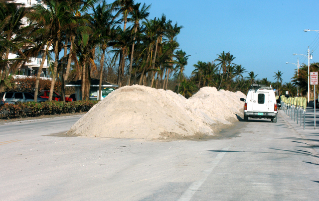 [Hurricane Wilma] Key West, FL, November 4, 2005 -- Mounds of sand are piled up in the middle of the street by city workers, adjacent to the ocean.  The sand covered the street as a result of Hurricane Wilma.  Jocelyn Augustino/FEMA