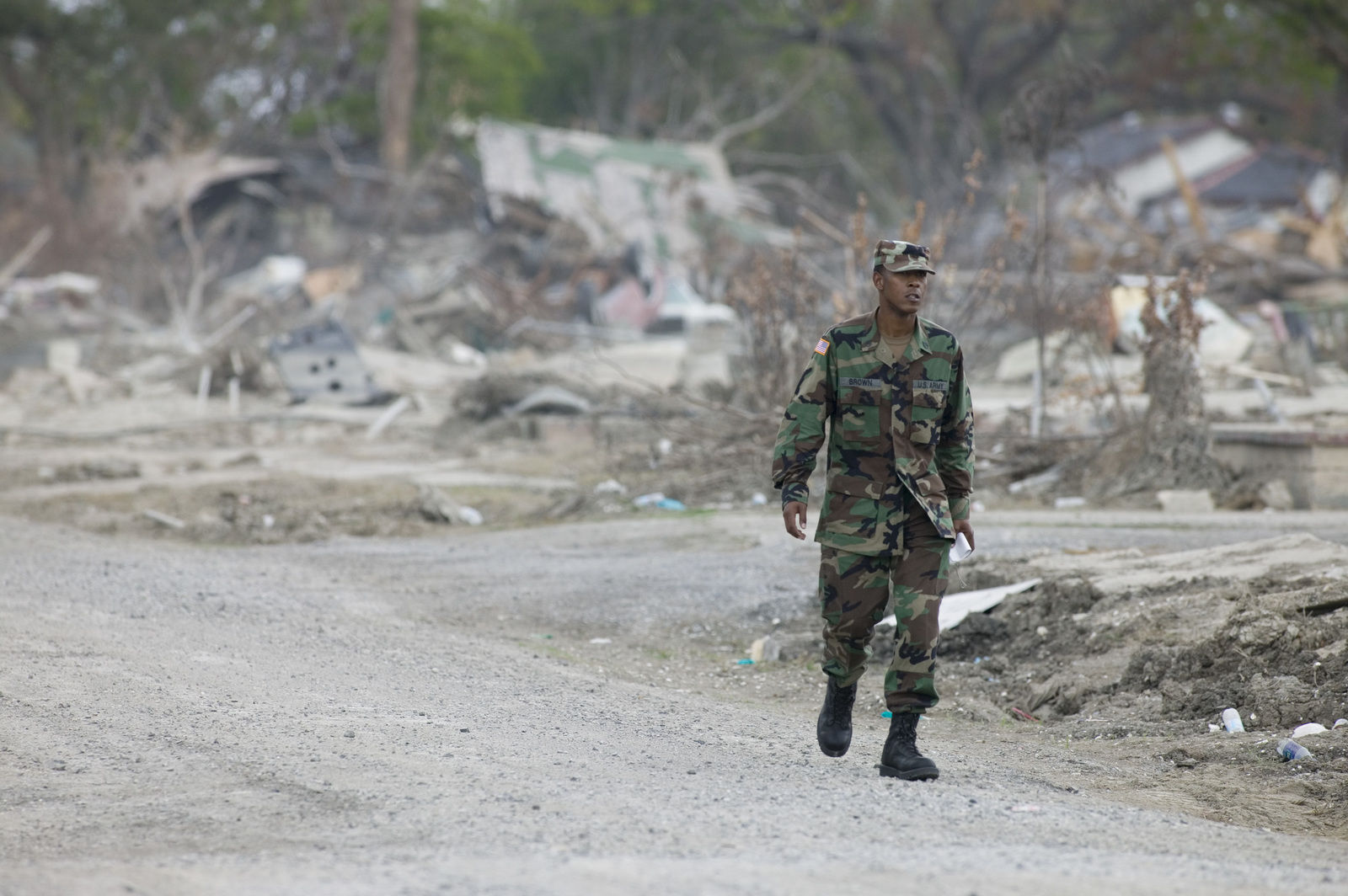 [Hurricane Katrina] New Orleans, LA., 11/05/2005-- A National Guardsman walks through a residential area that was reduced to debris.  The military was called on to help patrol the Lower 9th Ward following Hurricane Katrina.  Andrea Booher/FEMA