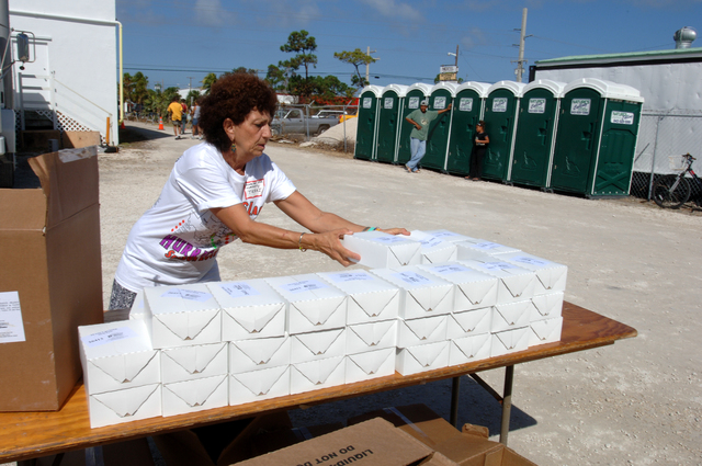 [Hurricane Wilma] Big Pine Key, FL, November 5, 2005 -- Terri Miller, a volunteer at the Disaster Recovery Center set up at the Habitat for Humanity Home Center, arranges food available to local residents impacted by Hurricane Wilma.  Jocelyn Augustino/FEMA