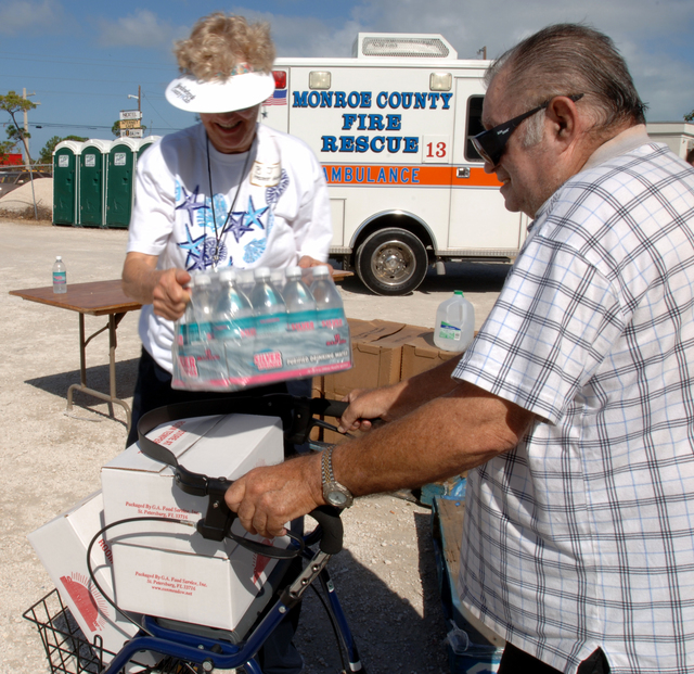 [Hurricane Wilma] Big Pine Key, FL, November 5, 2005 -- Volunteer Betty Fuller, left, gives water to James P. Napoli at the Disaster Recovery Center set up at the Habitat for Humanity Home Center.  Representatives from a variety of agencies are onsite to help residents impacted by Hurricane Wilma.  Jocelyn Augustino/FEMA