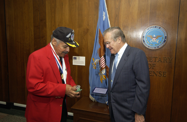 Former U.S. Air Force 2nd LT. William Wheeler (center), a Tuskeegee AIRMAN, points out a detail on an oil painting depicting various parts of the history of the Tuskeegee Airmen, that is on display in the Pentagon, to U.S. Air Force (retired) mater SGT. Ezra Hill (front, right) on Nov. 10, 2005. The Tuskeegee Airmen are visiting the Pentagon to receive a briefing about the current state of the U.S. Air Force and U.S. global operations, and then to have lunch with the Honorable Donald H. Rumsfeld, U.S. Secretary of Defense. (U.S. Air Force photo by MASTER SGT. James M. Bowman) (Released)