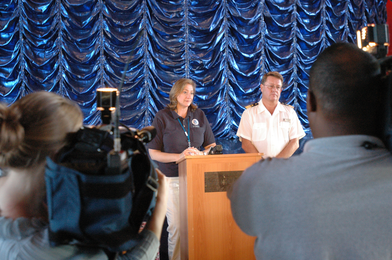 [Hurricane Katrina] Pascagoula, Miss., November 10, 2005 -- FEMA External Affairs Officer Mary Hudak (left) and Carnival Cruise Line representative Andrew Mace address the media aboard the cruise ship Holiday.  The media toured the ship to see how it is being used to house Mississippi residents displaced from their homes by Hurricane Katrina.  FEMA/Mark Wolfe
