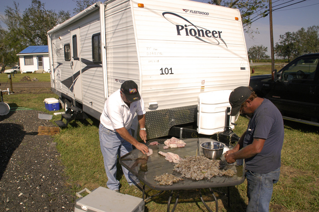 [Hurricane Katrina] Diamond, LA, 11-12-05 -- Mike Scarabin & Pimmy Poyadou clean fish and shrimp in at their FEMA Travel Trailer. Plaquemine Parish and FEMA teamed together to provide Travel Trailer housing for Plaquemine Government officals that are victims of Hurricane Katrina.  MARVIN NAUMAN/FEMA photo