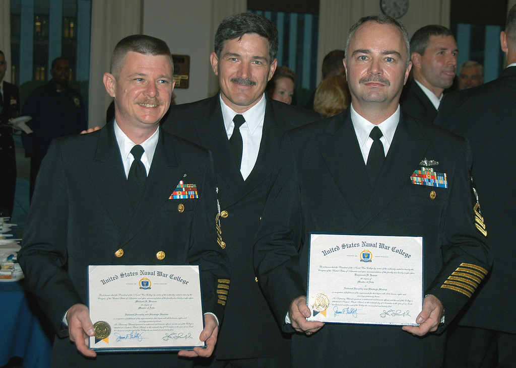 US Navy (USN) MASTER CHIEF PETTY Officer of the Navy (MCPON) Terry Scott (center), congratulates MASTER CHIEF PETTY Officer (MCPO) Michael C. Bruner (left), and MCPO Raymond D. James, after graduating from the Naval War College in Newport, Rhode Island (RI). MCPO Bruner and James are the first enlisted members to graduate from the Naval War College, the Navy's highest educational institution