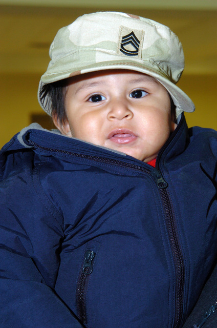 The young son of US Army (USA) Sergeant First Class (SFC) Lorenzo Castilla, poses for a photograph wearing his fathers military hat, during a Welcome Home Ceremony for Soldiers assigned to the 263rd Personnel Services Detachment, at Lansing, Michigan (MI). The Soldiers are returning from a one-year deployment to Iraq, in support of Operation IRAQI FREEDOM. (A3695)