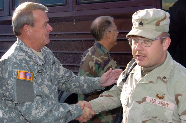 US Army (USA) Brigadier General (BGEN) Robert V. Taylor (foreground left), Assistant Adjutant General for the Army; greets a USA Sergeant (SGT) from the 263rd Personnel Services Detachment, Michigan Army National Guard (MIARNG), as he arrives at home in Lansing, Michigan (MI), returning from a one-year deployment to Iraq, in support of Operation IRAQI FREEDOM. USA Major General (MGEN) Thomas Cutler, Michigan State Adjutant General, is pictured in the background. (A3695)