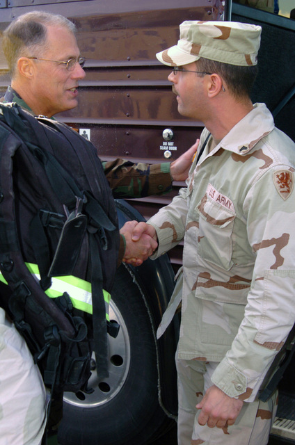 US Army (USA) Major General (MGEN) Thomas Cutler (left), Michigan State Adjutant General, welcomes a USA Sergeant (SGT) from the 263rd Personnel Services Detachment, Michigan Army National Guard (MIARNG), arriving home at Lansing, Michigan (MI), returning from a one-year deployment to Iraq, in support of Operation IRAQI FREEDOM