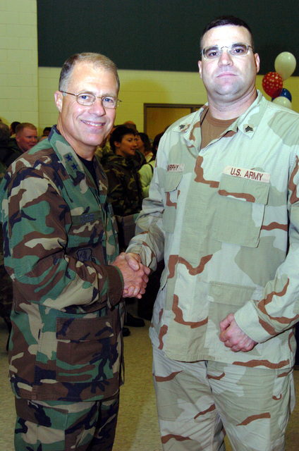 US Army (USA) Major General (MGEN) Thomas Cutler (left), Michigan State Adjutant General, welcomes home USA Sergeant (SGT) Charles Murphy, 263rd Personnel Services Detachment, Michigan Army National Guard (MIARNG), as he arrives home at Lansing, Michigan (MI), returning from a one-year deployment to Iraq, in support of Operation IRAQI FREEDOM. (A3695)