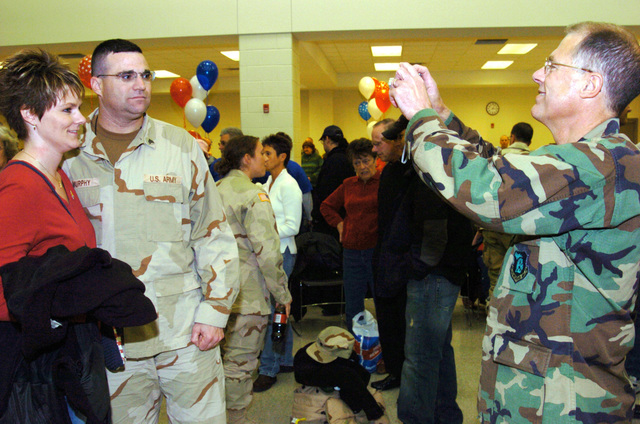 US Army (USA) Major General (MGEN) Thomas Cutler (right), Michigan State Adjutant General, uses a digital camera to photograph USA Sergeant (SGT) and Mrs. Charles Murphy, during a Welcome Home Ceremony, for Soldiers assigned to the 263rd Personnel Services Detachment, Michigan Army National Guard (MIARNG), at Lansing, Michigan (MI). The Soldiers are returning from a one-year deployment to Iraq, in support of Operation IRAQI FREEDOM. (A3695)