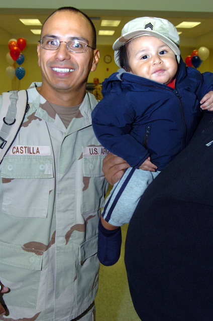 US Army (USA) Sergeant First Class (SFC) Lorenzo Castilla a member of the 263rd Personnel Services Detachment, Michigan Army National Guard (MIARNG), at Lansing, Michigan (MI), poses for a photograph with his son, during a Welcome Home Ceremony for Soldiers returning from a one-year deployment to Iraq, in support of Operation IRAQI FREEDOM. (A3695)