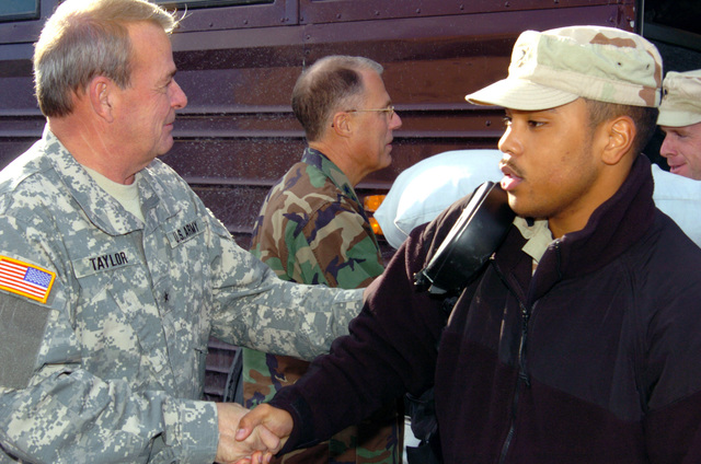 US Army (USA) Soldiers assigned to the 263rd Personnel Services Detachment, Michigan Army National Guard (MIARNG), are meet by high-ranking officials as they arrive at their home in Lansing, Michigan (MI), returning home from a one-year deployment to Iraq, in support of Operation IRAQI FREEDOM. Pictured left-to-right: US Army (USA) Brigadier General (BGEN) Robert V. Taylor (left), Assistant Adjutant General for the Army; USA Major General (MGEN) Thomas Cutler, Michigan State Adjutant General, and USA SPECIALIST (SPC) Kyle Whitehead, 263rd Personnel Services Detachment. (A3695)