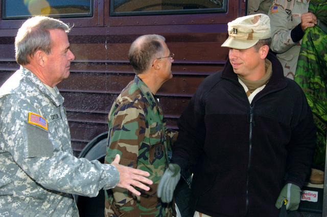 US Army (USA) Soldiers assigned to the 263rd Personnel Services Detachment, Michigan Army National Guard (MIARNG), are meet by high-ranking officials as they arrive at their home in Lansing, Michigan (MI), returning home from a one-year deployment to Iraq, in support of Operation IRAQI FREEDOM. Pictured left-to-right: US Army (USA) Brigadier General (BGEN) Robert V. Taylor (left), Assistant Adjutant General for the Army; USA Major General (MGEN) Thomas Cutler, Michigan State Adjutant General, and USA Captain (CPT) Brian Bonney, 263rd Personnel Services Detachment. (A3695)