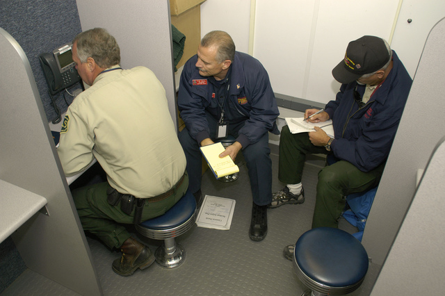 [Hurricane Rita] Cameron, LA, 11-18-05 -- Field FEMA operations Mike Dietrich, Tim Ball, and Sam Willbanks do a conferance call in the FEMA sponsored MCI phone/communication trailer.  The FEMA sponsored MCI communication van provides phone and internet service for the whole community which is totaly without service.  MARVIN NAUMAN/FEMA photo