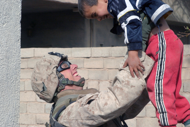 US Marine Corps (USMC) Private First Class (PFC) Erskine Blanton, Fox Company (F CO), 2nd Battalion (BN), 2nd Marine Regiment (MAR REGT), plays with an Iraqi child while on a security halt during operations in Kharma, Iraq, during Operation IRAQI FREEDOM