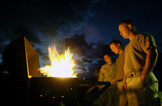 US Navy (USN) PETTY Officer Third Class (PO3) Jessica Young (left), PO3 Arthur Perry, and PETTY Officer Second Class (PO2) Ron Brown (right) stand over a makeshift grill during downtime at a US military camp in Harar, Ethiopia. USN Construction Battalion (SEABEE) with Naval Mobile Construction Battalion 3 (NMCB 3), Port Hueneme, California (CA), dug three wells and are staging to drill several hand-pump wells, to provide thousands of Ethiopians and their livestock with potable water. US Army (USA) Soldiers from 1ST Battalion (BN), 294th Infantry Division (ID), Bravo Company (B CO), Guam (GU), provide force protection at the camp and well sites so that the Seabees can concentrate their...