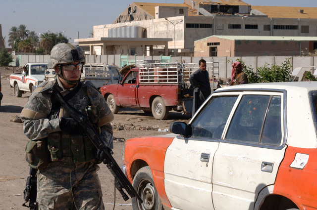 A soldier from HHC Company, 2/22 INF, 10th Mountain Division pulls rear security during a search of the Baghdad market area. (U.S. Army photo by PFC. Nathaniel Lawrence) (Released)