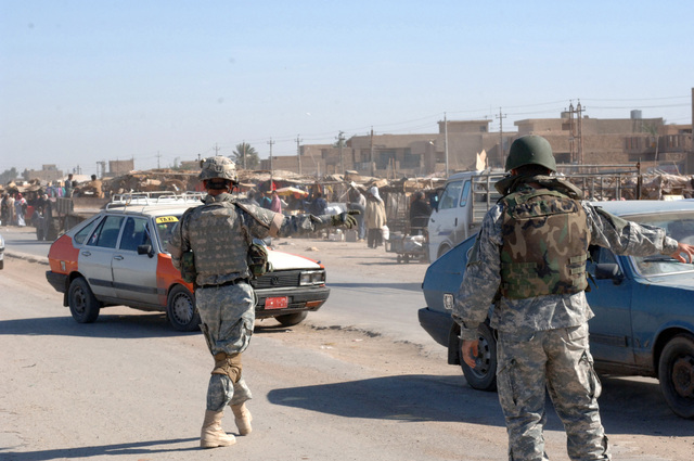 U.S. Army SGT. 1ST Class Wiser and an interpreter direct traffic around a convoy during a dismounted patrol of Baghdad's market area. (U.S. Army photo by PFC. Nathaniel Lawrence) (Released)