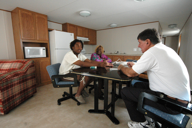 [Hurricane Katrina] Gautier, Miss., November 24, 2005 -- Sereta Haynes (center) and her grandson speak with FEMA Public Information Officer Michael Raphael (right) in their new FEMA mobile home on Thanksgiving Day.  FEMA is utilizing various methods to temporarily house residents displaced by Hurricane Katrina.  Mark Wolfe/FEMA