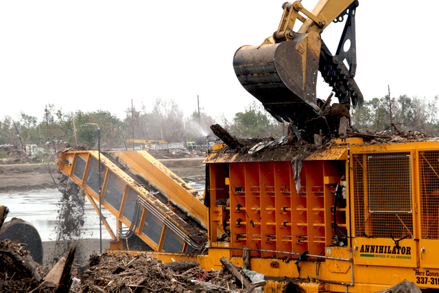 [Hurricane Katrina] Empire, LA, December 7, 2005 - Debris is collected and deposited at the Plaquemines Parish Debris Grinding Site.  A crane transfers the debris into the grinder where it is ground to one fourth of its original volume, sprayed with water to reduce airborne residue and travels out of the grinder by conveyor belt into a pile where it is bulldozed into a pit that can hold over 3 million cubic yards of material.  Robert Kaufmann/FEMA