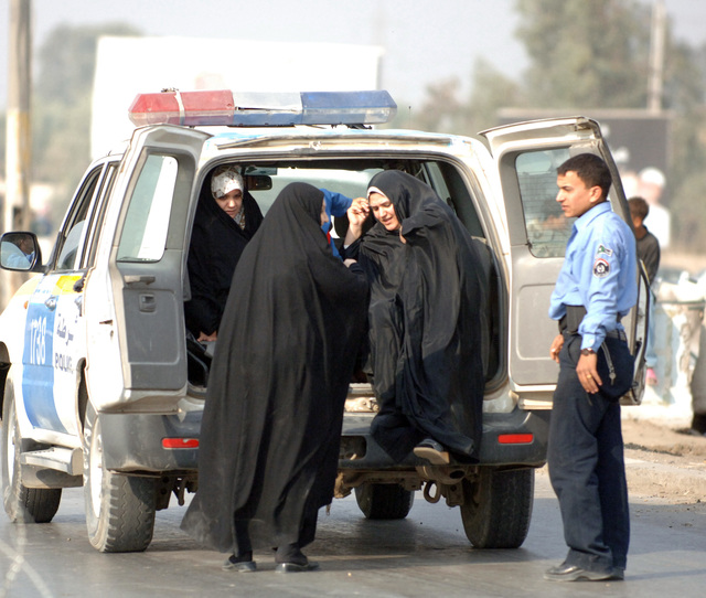 A group of Iraqi women are escorted to a polling site by Iraqi police who were mobilized to polling sites in Iraq's first official democratic elections Dec. 15, 2005 in Taji, Iraq.The Iraqi Police as well as the Iraqi Army were scheduled to vote earlier than the rest of the populace in order to provide added security during Iraq's general elections.(U.S. Army photo by PVT. Ronald R. Gaete) (Released)