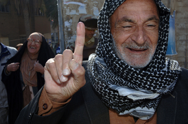 An Iraqi senior citizen shows his index finger after voting for the Iraqi parliamentary government elections in East Baghdad, Iraq on Dec. 15, 2005.  These elections will set the path to a future democracy in Iraq for the next four years.(U.S. Army photo by SPC. Teddy Wade) (Released)